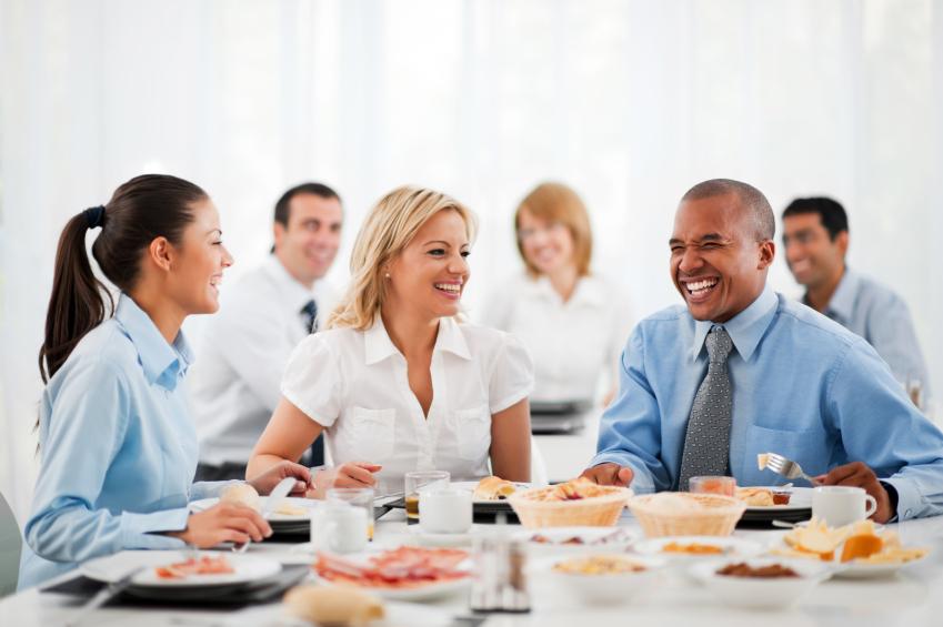 lachende Menschen essen zusammen
