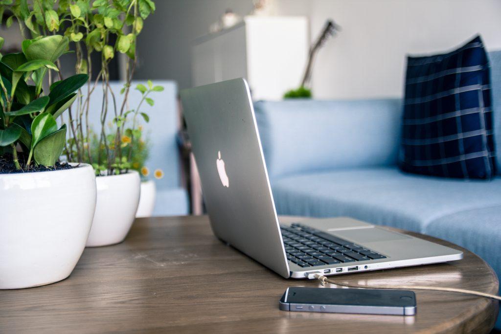 Laptop und Handy auf Couchtisch